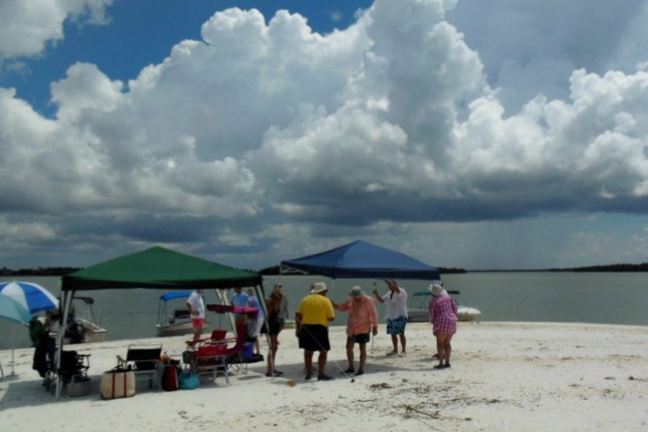 Photo, beach picnic with several adults under and around some beach awnings and umbrellas. In background are 3 boats pulled up to the beach.